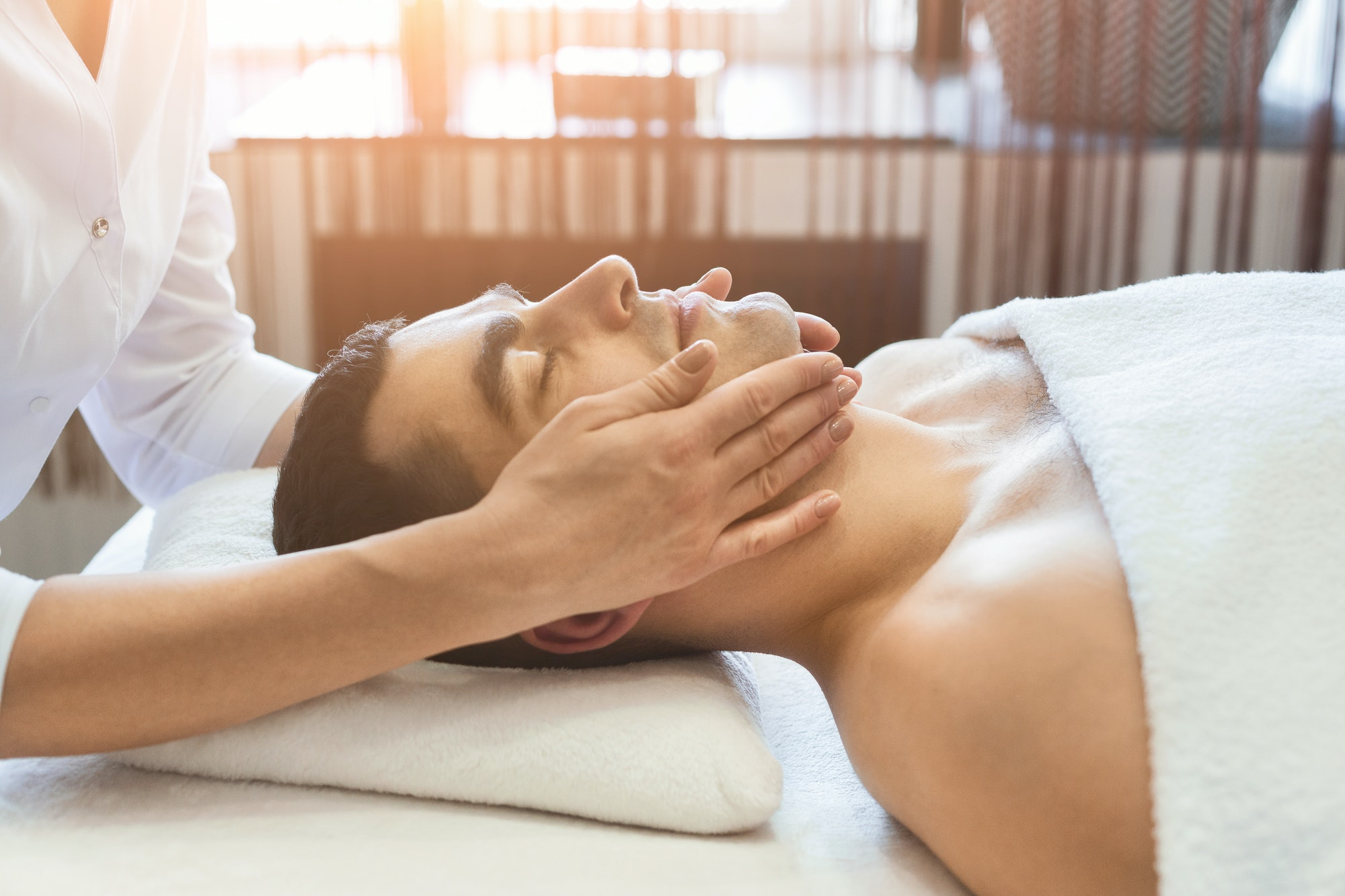 Man getting professional facial massage at spa salon